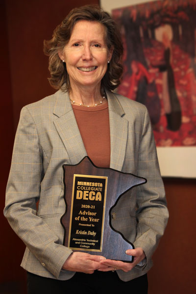 Kris Daby holds her 2021 DECA Advisor of the Year plaque