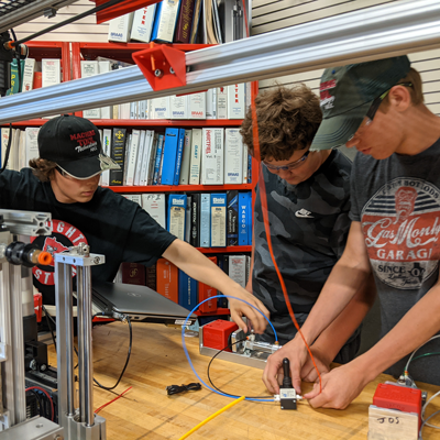 Three students work on an assembly in the Mechatronics classroom