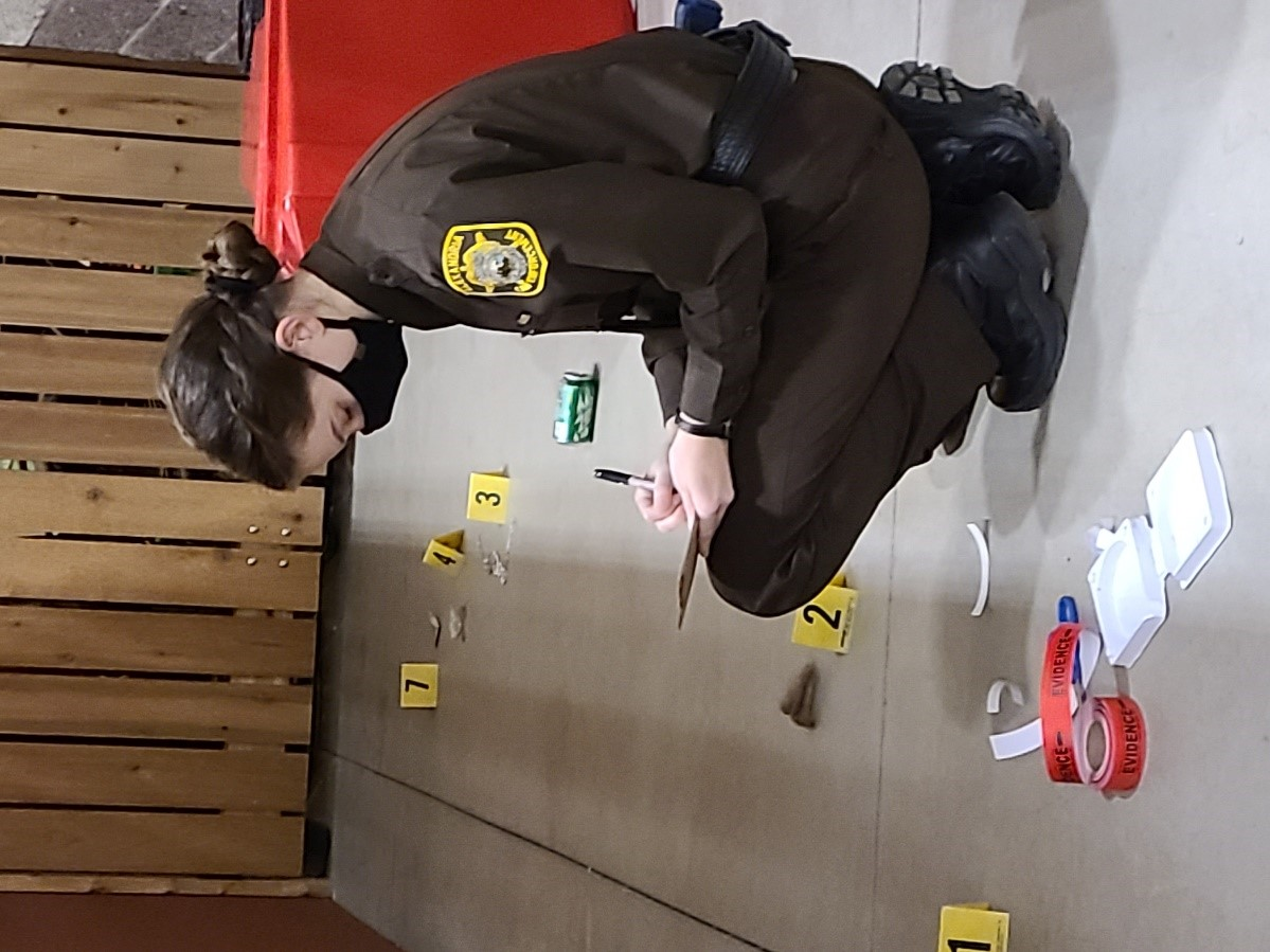 Abigail Mumme tags evidence at a simulated crime scene as part of the 2021 sexual assault lab.