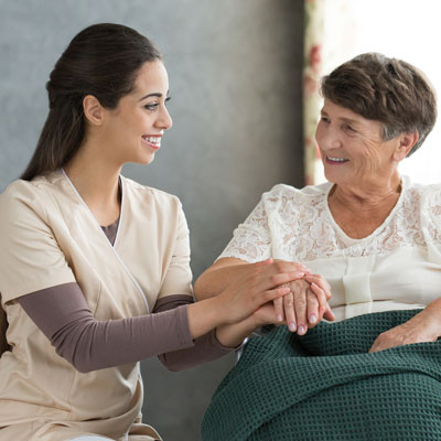 Nursing Assistant or Home Health Aide sits with elderly woman