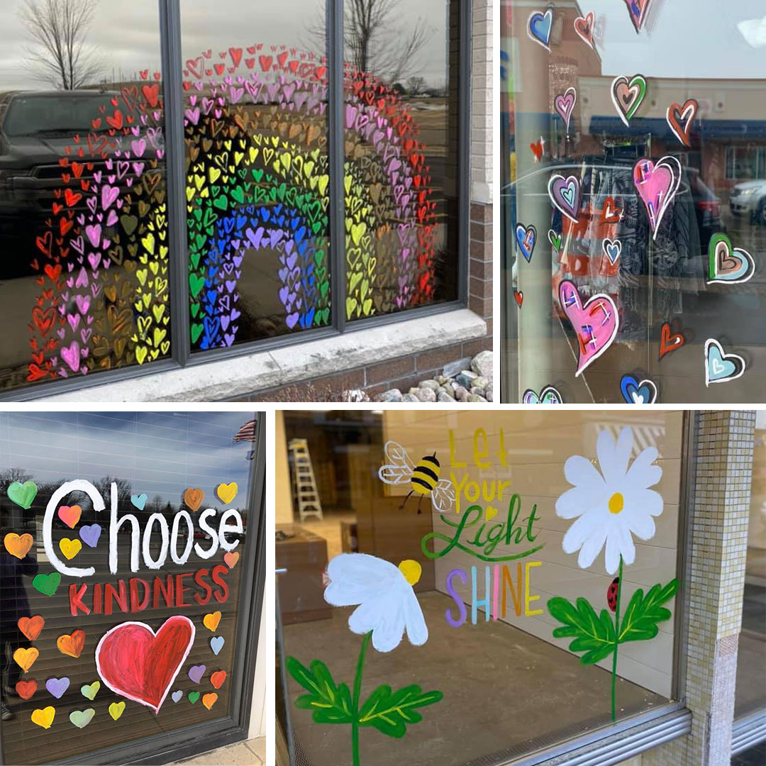 Hearts and inspirational messages painted on windows of area businesses