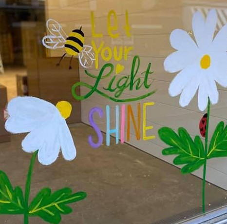 """Painting on window of flowers and bees with text """"Let your light shine"""""""