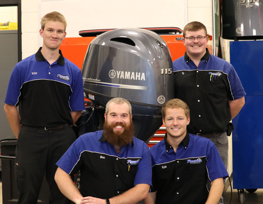 Powersports students pose with donated outboard motor